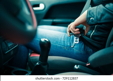 passenger woman fastening seat belt in the car, safety concept (color toned image)