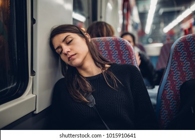 Passenger woman sitting in her seat and sleeping inside a train/bus while traveling.Tired exhausted woman taking a nap in public transportation.Falling asleep during a long ride.