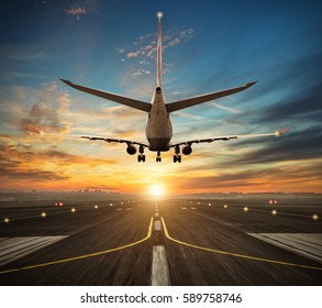 Passengers airplane landing to airport runway in beautiful sunset light, silhouette of modern city on background