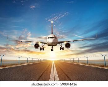 Passengers airplane landing to airport runway in beautiful sunset light