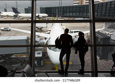 Passengers at the airport look through the window to the plane. Silhouettes of travelers against the backdrop of a passenger aircraft.