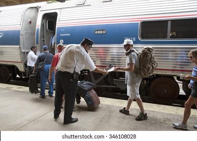 PASSENGERS BOARDING AN AMTRAK TRAIN FLORIDA USA NOVEMBER 2013 -  Railroad conductor and station staff assist passengers to board an Amtrak train. DeLand Station Florida USA