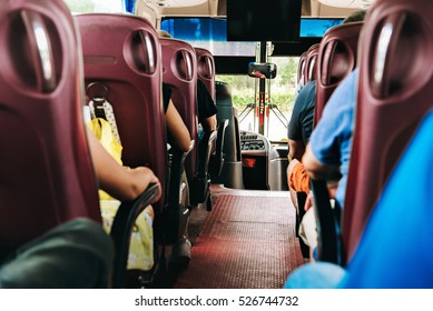 the passengers in the bus during the trip. travelers sit with their backs to the frame, their faces are not visible. the bus is equipped with a TV