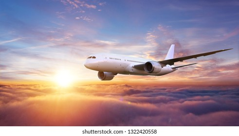 Passengers commercial airplane flying above clouds in sunset light.