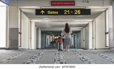 Passengers are going to the gate No. 21 - 26 for departure at the airport terminal.