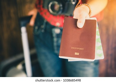Passengers hold passports and travel luggage tickets to show to inspectors.