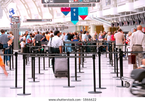 Passengers lining up at check-in counter at the modern international airport, no faces visible