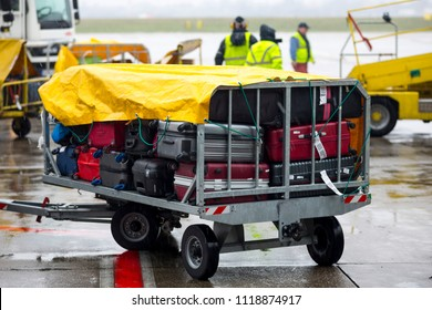 Passengers' luggage is seen covered from the rain on a cart near the airplane.