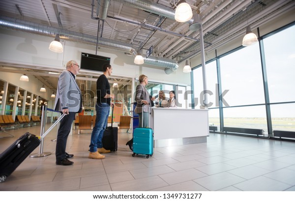 Passengers With Luggage Waiting At Reception In Airport