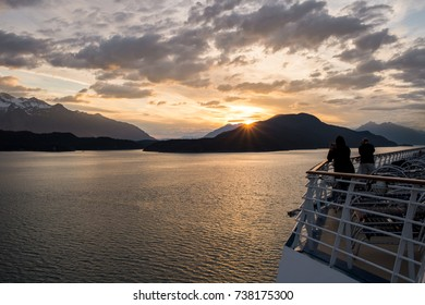 Passengers on board a Cruise Ship enjoy the late sunset in Alaska