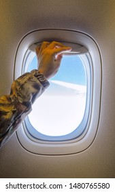 Passengers are opening airplane windows. Hand pulling down or up window blinds during flight.