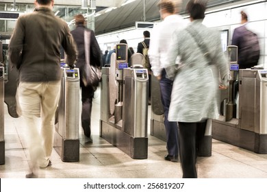 Passengers passing through automatic ticket barriers at underground station