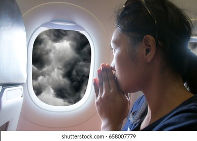 Passengers praying in a flying aircraft while looking out of the window on storm clouds.