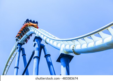 passengers restrained in seats of steel roller coaster trains climbing to a higher place on white steel trail