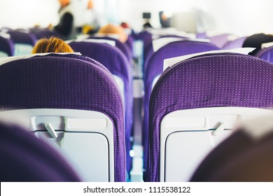 passengers are sitting in the blue armchairs of the aircraft during the flight, the view from the back of tourists flying into a vacation trip travel, airplane inside interior, voyage concept