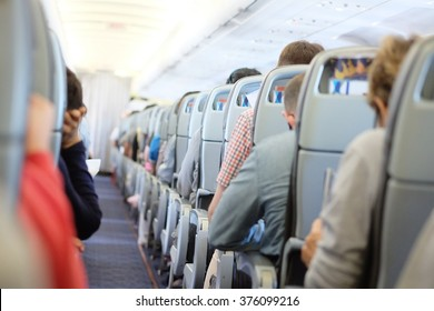 Passengers are sitting and sleeping on an airplane. They get stuck in their seat in a long and boring flight.