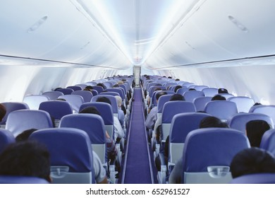 Passengers traveling by a plane, shot from the inside of an airplane