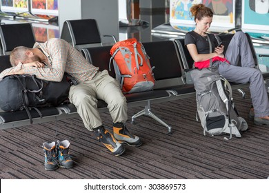 Passengers waiting for the air flight at airport terminal. Man and woman sitting in chairs line sleeping browsing smart phone internet casual dress code heavy boots backpacks luggage building interior