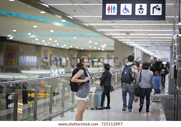 Passengers watch the  toilet sign in airport.Toilets icon. Public restroom signs with a disabled access symbol. Interior of airport terminal.