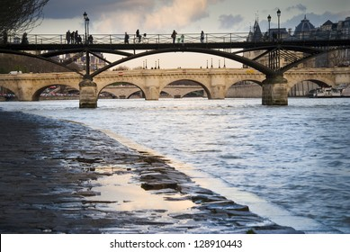 Passerelle des Arts over River Seine in Paris, France. Silhouettes of people walking on it. Pont Neuf (the oldest bridge in Paris) in the distance.