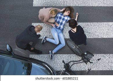 Passersby helping an unconscious casualty of a car accident lying next to the bike