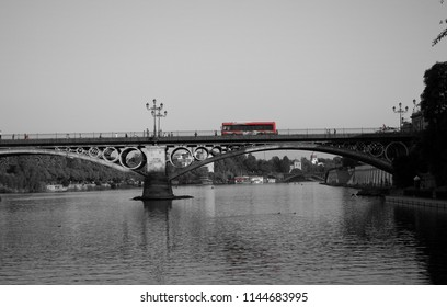 passes the red bus over the triana bridge on the guadalquivir river in Seville Spain