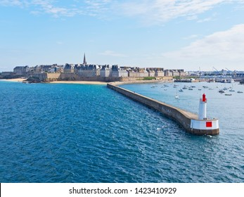 Passing the curved breakwater of Saint Malo, with the city and its walls in the background as we leave port in the morning sunshine