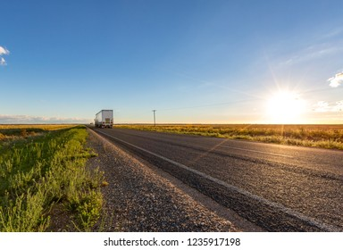 A passing truck travels along a straight road in the New South Wales countryside where there are few trees and  little to be seen across endless farmlands to the horizon.