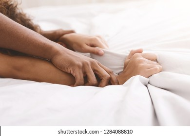 Passion in bed. African-american couple hands pulling white sheets in ecstasy, closeup