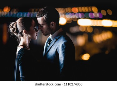 passion couple in love stands against the lights of a night city, hugs kisses