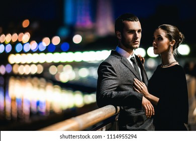 passion couple in love stands against the lights of a night city, hugs, handsome man looks straight, woman looks at him