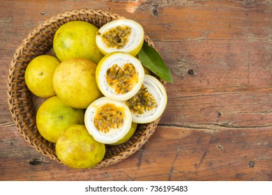 Passion fruit in bamboo basket. Tropical fruit. Sour taste, high vitamin. Diet dessert. On wooden table. Top view with copy space.