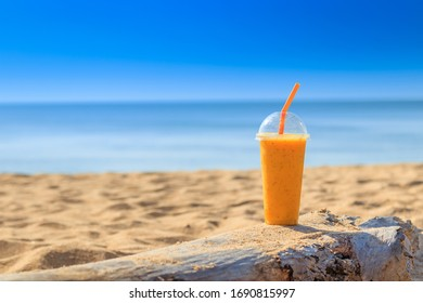 Passion fruit juice  with Straw in glass on sand beach at Phuket  Thailand . summer concept