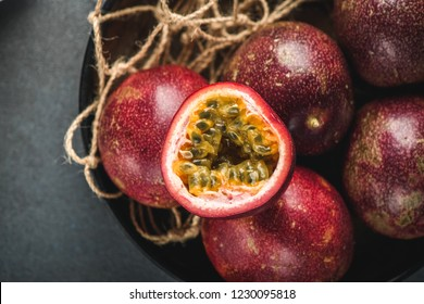 Passion fruit or maracuja from exotic tropical countries on table. Cutting pulp with seeds and juice