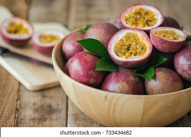 Passion fruit on wood bowl put on wood table in side view for background or wallpaper. Prepare fresh fruit on cutting board for homemade dessert or salad cooking. Ripe passion fruit so sweet and sour.