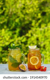 Passion fruit and orange lemonade cocktails. Fresh lemon, small flower, passion fruit and mint decoration. Cold refreshing drinks or beverages in glass jars with ice on white table.
