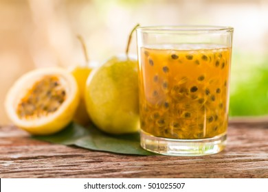 Passion fruits half and juice with leaves on the vintage wooden background. Closeup, Select focus.