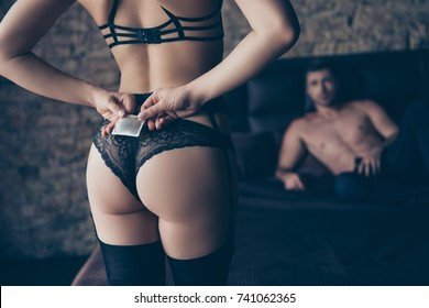Passion, pleasure, desire game, health. Close up cropped photo of prelude, hot seductive fit booty bum shape, hips in black elegant lingerie, legs, holds hides condom wrapped pack, guy lying in bed