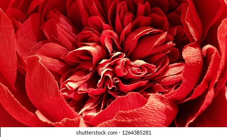 Passion red lush peony flower made from crepe paper. Paper peony petals closeup. Valentines Day background. Romantic decorations. Wedding bouquet decor. Romantic love themed backdrop.