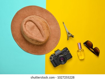 Passion for travel, wanderlust concept. Trip to France, Paris. Felt hat, film camera, sunglasses, perfume bottle, souvenir statue of Eiffel Tower layout on a colored paper background. Flat lay.