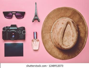 Passion for travel, wanderlust concept. Trip to France, Paris. Felt hat, film camera, sunglasses, passport, perfume bottle, souvenir statuette of the Eiffel Tower layout on a pink  paper background.