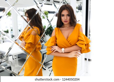 Passion woman wearing yellow evening dress with sleeves and decollete. Hands together, watches and neckless. Long dark hair lying o the back.Bright party makeup and fashion style. Reflecting in mirror