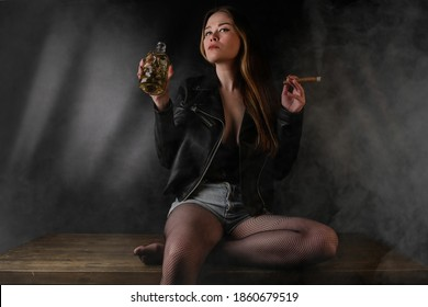 Passionate badass lady with cigar in one hand and bottle of alcohol in another one. Liquor bottle formed as human scull. Woman wears sexy stockings, black leather jacket and dark lacy underwear.
