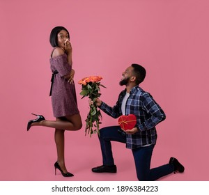 Passionate black man giving his sweetheart bouquet of roses and heart shaped gift for Valentine's Day on pink studio background. Happy woman getting flowers and present from her boyfriend, full length