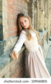 Passionate blue-eyed young girl dreaming near ancient brick wall