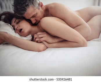 Passionate couple in bed having sex. Young man and woman making love in bedroom.