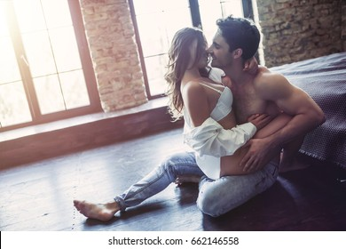 Passionate couple in bedroom is having sex on floor.