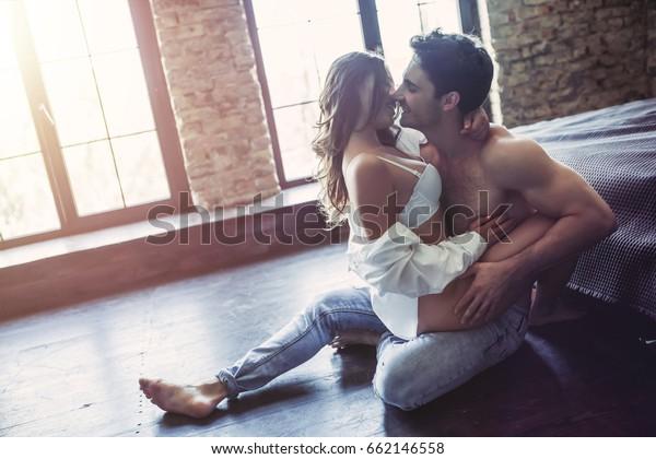 寝室にいる情熱的なカップルが、床でセックスをしている。