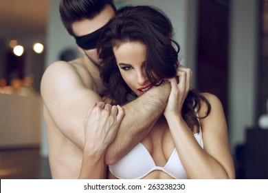 Passionate couple foreplay in luxury flat, sexy woman in bra bite man arm, young lover with lace eye cover