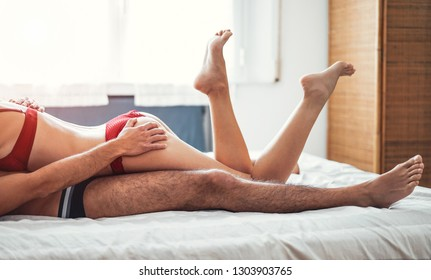 Passionate couple having sex on a bed at home - Loving intimate and romantic moments of lovers in the bedroom - Concept of people, love, relationship and sexuality